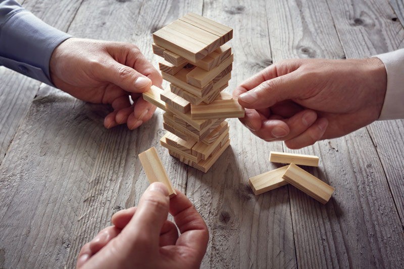 several people's hands playing Jenga game