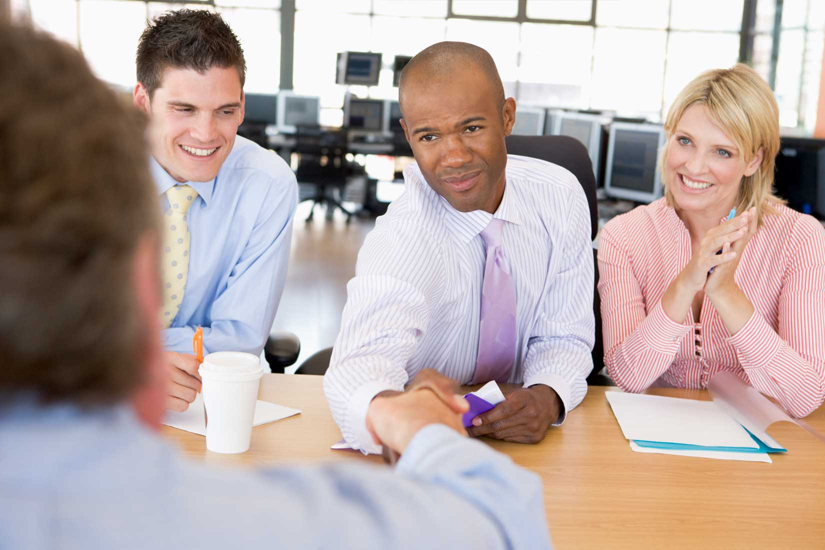 HR recruiting meeting, 2 people shaking hands and smiling