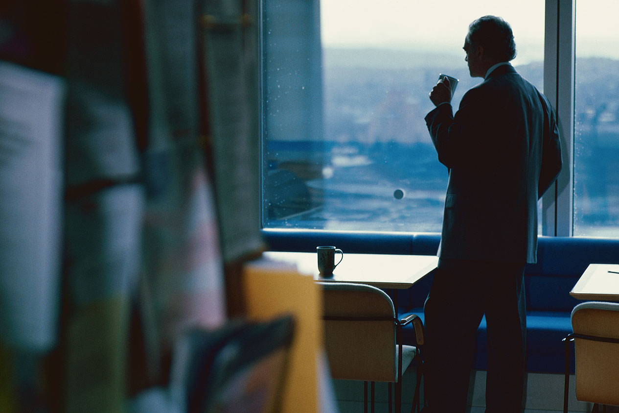 Business Owner Manager Looking out window with coffee