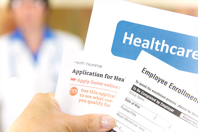 Open enrollment healthcare benefits forms with a medical doctor in the background