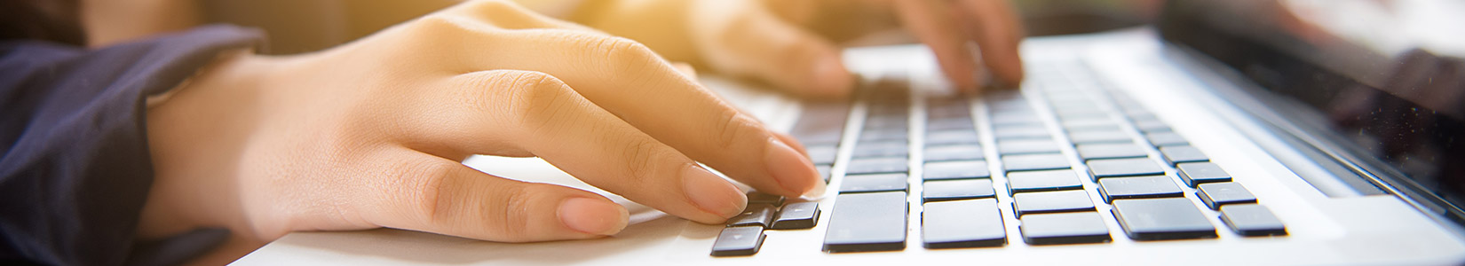 Woman typing on computer logging into her HR Employee Website Intranet Portal