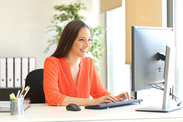 Businesswoman wearing an orange blouse working typing in a desktop computer at office viewing customized employee website