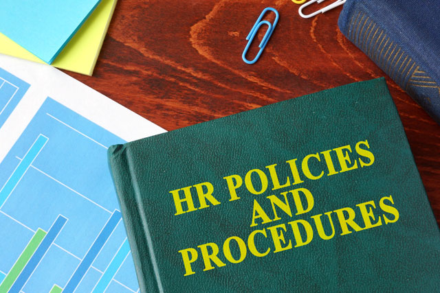 HR policies and procedures handbook on table