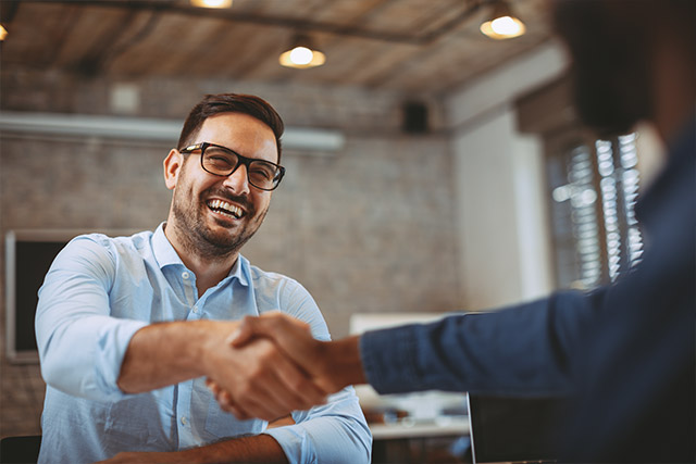 Man getting hired after recruiting, close up of handshake in the office