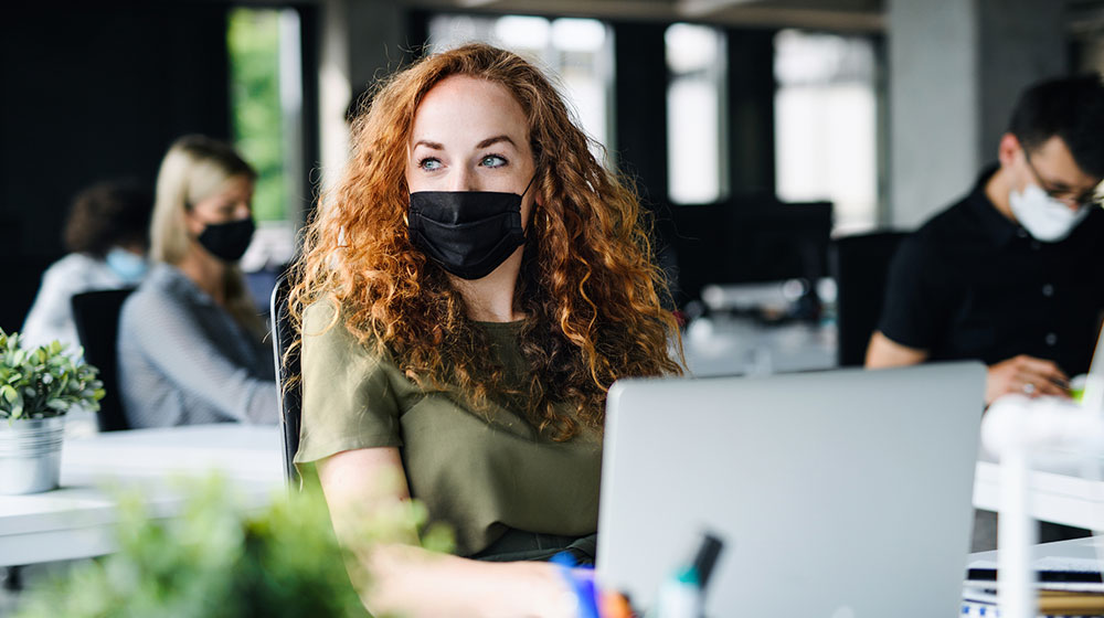 Female employee in office wearing a mask.